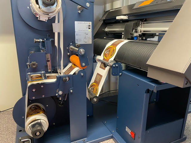Etikettmaskin som viser konturskjæring og pakking på rull