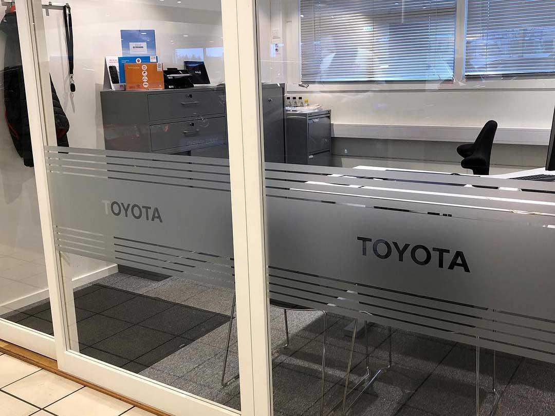 Frostet folie på vindu innendørs, med Toyota-logo