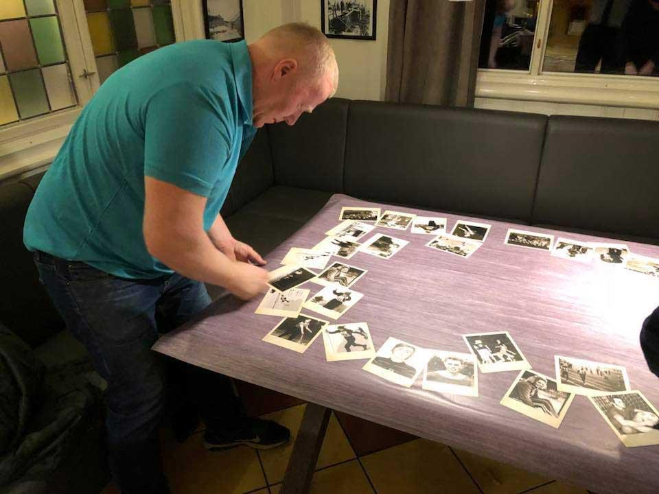 Daglig leder Olav folierer et bord, me trebakgrunn og diverse bilder som ser ut som de ligger løst på toppen